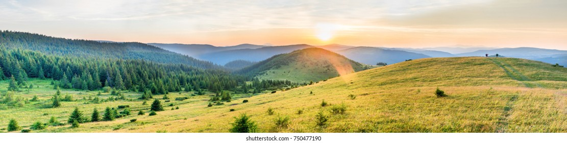 Panorama of sunset in the mountains with forest and sun on dramatic sky
