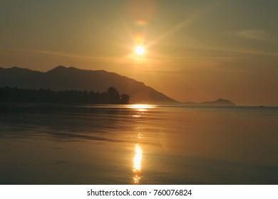 Panorama of sunset on Koh Pha Ngan island, Thong Sala beach, Thailand. Silhouette view