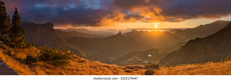 A panorama of a sunset over Gran Canaria, Spain. The Roque Nublo is visible on the left side. Tenerife is visible in the background.