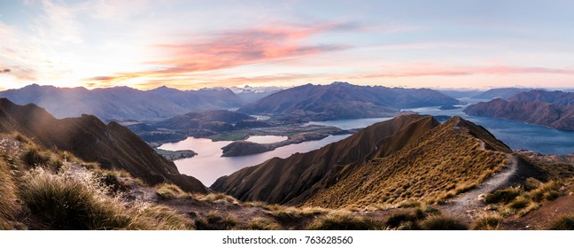 panorama at sunset of Roys Peak between Wanaka and Queenstown with a lake and mount aspiring and cook of the new zealand alps on the background