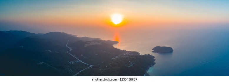 Panorama sunset sky, ocean, island. Aerial drone shot. Thailand. Breathtaking scene the bright sunset over the calm ocean and Ko Pha-ngan island in the Kingdom of Thailand. Perfect spiritual place.