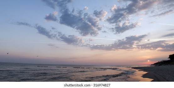 panorama of sunset or sunrise on beach with water reflection