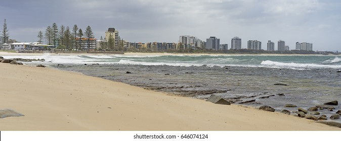 Panorama of Sunshine Coast foreshore at Alexandra Headlands Mooloolaba with surf waves, sand, beach, rocky seafront and cloudy sky