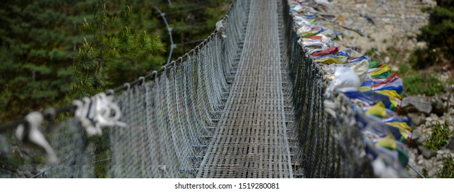 Panorama of suspension bridge on Everest base camp trek, Selective focus on Nepal prayer flags in the wind.