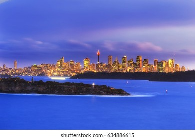 Panorama of Sydney city CBD in a distance along Sydney Harbour behind South Head with Hornby lighthouse at sunset.