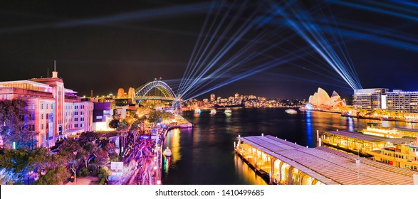 Panorama of Sydney harbour around Circular Quay and Sydney Harbour Bridge during Vivid Sydney light show with blue laser beams drawing lines in the night sky.