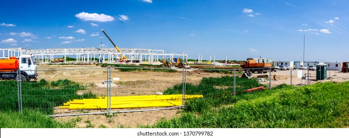 Panorama is taken with wide lens, unfinished concrete edifice under construction, people are working with machinery.