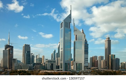 Panorama of tall Skyscrapers in skyline of Dubai against blue sky.