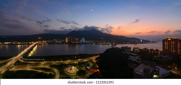 Panorama of the Tamsui and Bali districts along the river in New Taipei City at sunset with a crescent moon and the planet Venus rising above Mount Guanyin