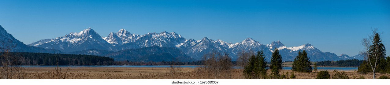 """Panorama of the  Tannheimer mountains from the """"Gehrenspitze"""" till the """"Breitenstein"""" with snow-capped summits, blue sky and the lake """"Bannwald"""" in the foreground"""