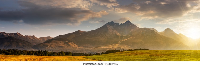 panorama of Tatra mountains in haze behind the forest and rural field in morning light