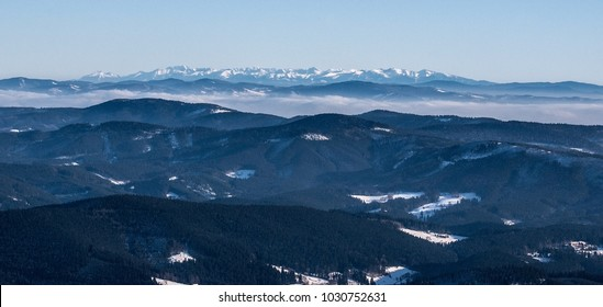 panorama of Tatra mountains range wthl lower mountain ranges on the front from Lysa hora hill in Moravskoslezske Beskydy mountains in Czech republic during winter day with clear sky