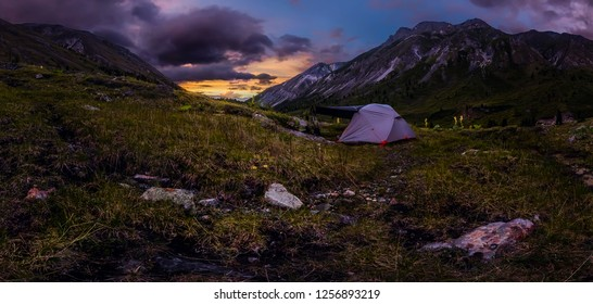 Panorama tent in the mountains on a background of purple clouds at sunset