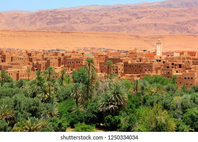 Panorama of the Tinghir oasis on the Todgha River in Morocco Africa with lush green palm trees and the Atlas mountains in the background.