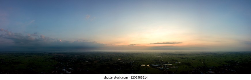 Panorama Top view Aerial photo from flying drone over village in Thailand.Top view beautiful Sunset with dramatic sky clouds.Sunrise with cloud over rice field.