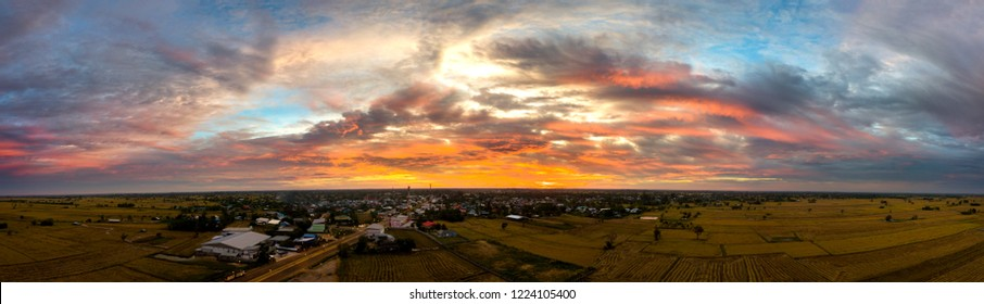 Panorama Top view Aerial photo from flying drone over village in Thailand.Sunrise with cloud over rice field.
