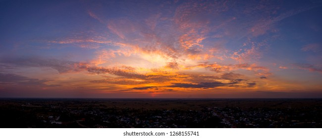 Panorama Top view Aerial photo from flying drone over village in Thailand.Top view beautiful Sunset with dramatic sky clouds.