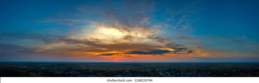 Panorama Top view Aerial photo from flying drone over village in Thailand.Cumulus sunset clouds with sun setting down on dark background.