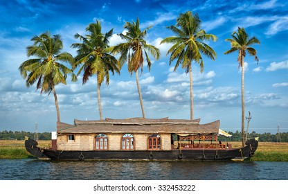 Panorama of tourist houseboat on Kerala backwaters with palms in background. Kerala, India