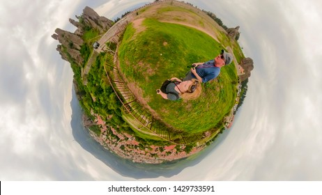 Panorama of tourists at Belogradchik Fortress with aerial views of village in rural Bulgaria.