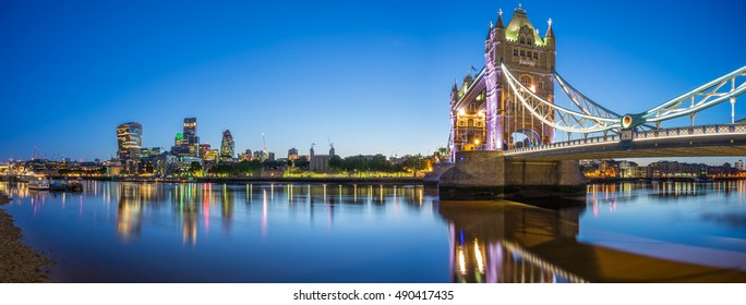 Panorama of Tower Bridge and illuminated skyscrapers in financial district in London, UK