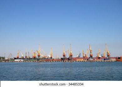 Panorama of trading seaport with cranes and cargoes