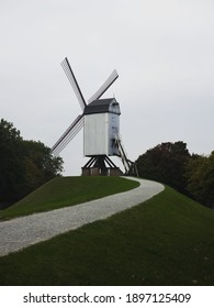 Panorama of trail path to historic traditional Bonne Chieremolen windmill post mill in Bruges West Flanders Belgium