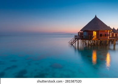 Panorama of tropical island resort with over water bungalows at night. Ari Atoll.