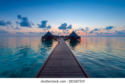Panorama of tropical island.  Turquoise water lagoons, coral reefs visible. Sunrise sky and clouds painted in pink. Tourist Resort Deluxe. Maldives