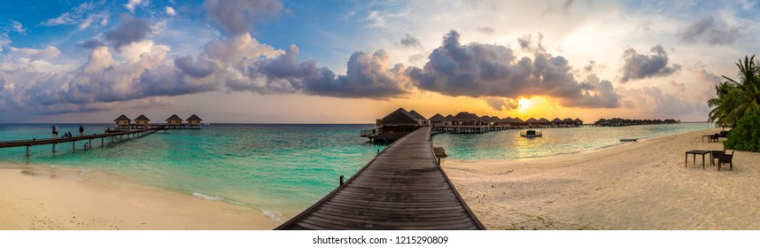 Panorama of Tropical sunset over bungalows at Tropical beach in the Maldives at summer evening