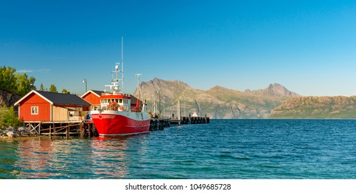 Panorama of tugboat or fishing boat at pier, Norway, Europe. Ship in foreground and blue sky and mountains in background. Scandinavia travel.