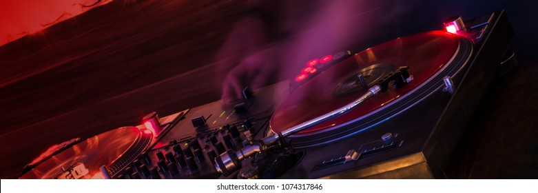 panorama of turntable with vinyl disk on fire, dj playing music
