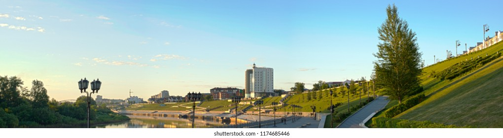 Panorama of Tyumen embankment at dawn. The rays of the rising sun illuminate the embankment with lawns and buildings.