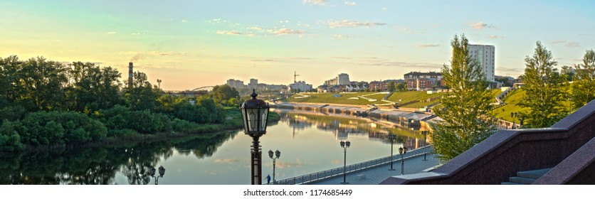 Panorama of Tyumen embankment at dawn. The rays of the rising sun illuminate the embankment with lawns and buildings. In the foreground is a street lamp and granite steps.