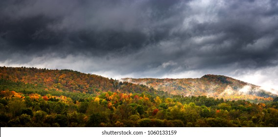 Panorama of a Vermont hillside on a foggy day during peak fall foliage season