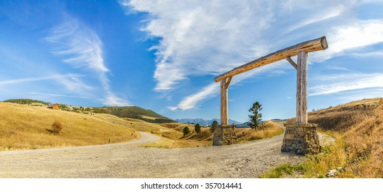 Panorama of a very large wooden archway on a dirt road in Montana
