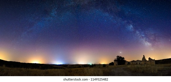 Panorama of the via lactea in the form of an arch over the ruins of an old Spanish castle next to the planet mars
