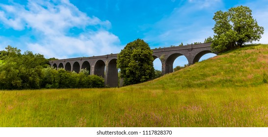 A panorama view across a grassy meadow of the derelict and abandoned viaduct near Catesby, Northamptonshire, UK