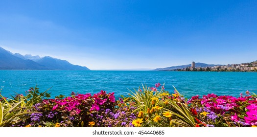 Panorama view of the Alps, Geneva lake and Montreux cityscape with colorful flowers in foreground on a sunny summer day, Canton of Vaud, Switzerland