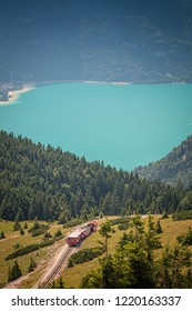 Panorama view in the Alps with small train climbing up to the hill.