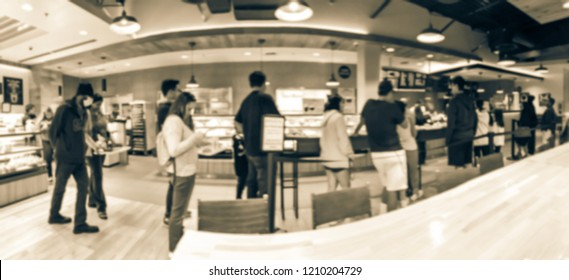 Panorama view Asian bakery shop in Texas, USA. Defocused multiethnic people waiting in line to check-out fresh baked bread in pastry shop counter.