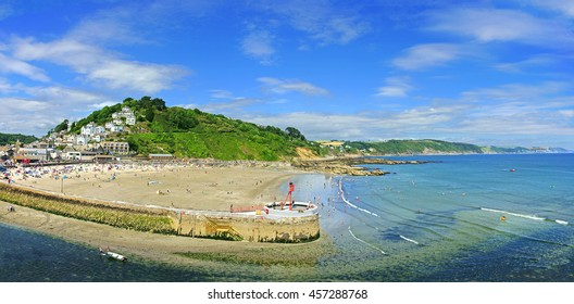 A Panorama view of Banjo Pier and Plaidy beach in summer with holiday makers enjoying the sea and surf, East Looe, Looe, Cornwall, England, UK