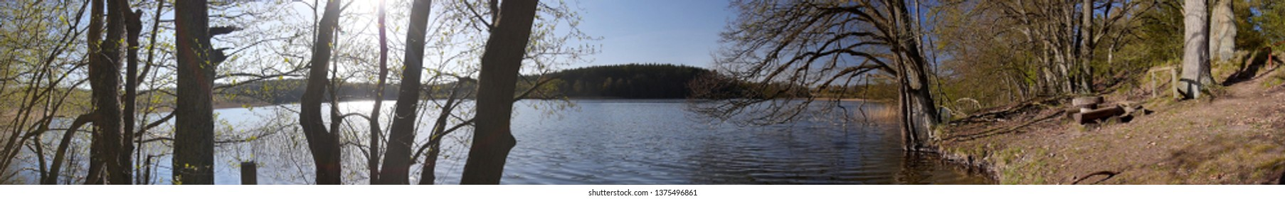 Panorama view of a bathing place at the water shore of a glacial lake in Mecklenburg-Western Pomerania with a picnic seat and surrounded by the forest