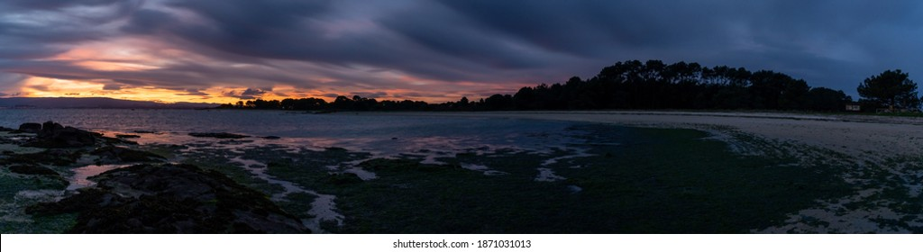 A panorama view of a beach at low tide under an overcast night sky with daybreak and colorful sunrise