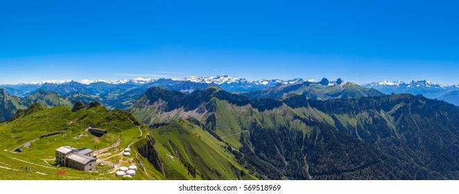 Panorama view of Bernese Alps from top of Rochers-de-Naye, with the cogwheel train station in foreground, near Montreux, Canton of Vaud, Switzerland
