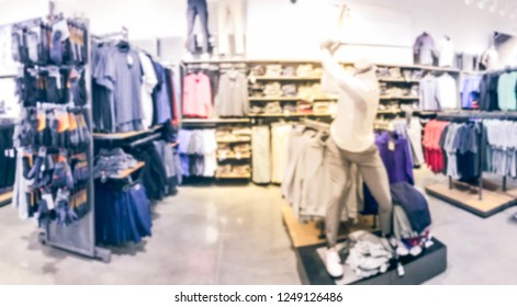 Panorama view blurred motion golf apparel, accessories and gear section with mannequin at sport retail store in America