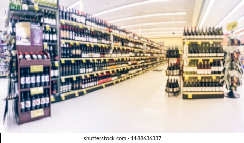 Panorama view blurred wine aisle with price tags at grocery store in Texas, America. Defocused rows of red, white wine liquor bottles on supermarket shelf. Alcoholic beverage abstract background