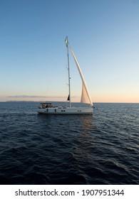 Panorama view of boat sailboat ship sailing into sunset mediterranean sea ocean water Mallorca Balearic Islands Spain