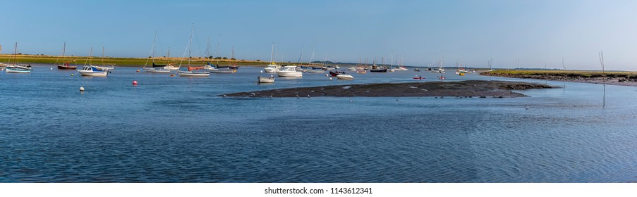 A panorama view of boats moored in Brancaster Bay near Burnham, Norfolk, UK