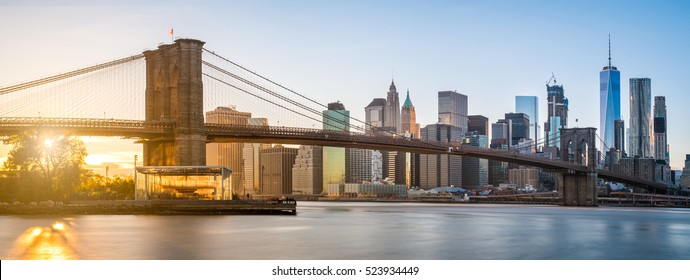 The panorama view of Brooklyn Bridge with Lower Manhattan in the background, lit by sunset